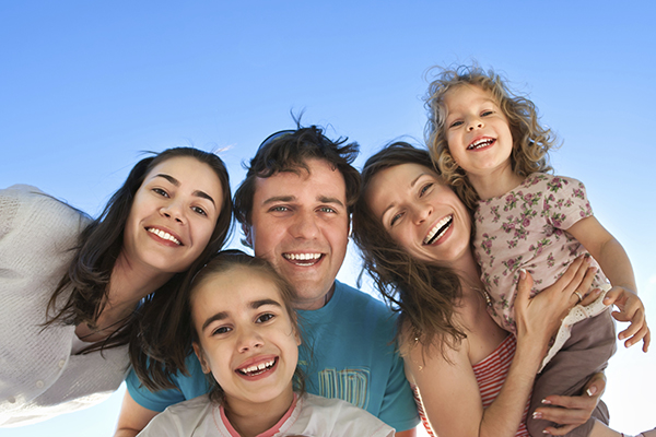 Happy family smiling about their dental care from Janice K. Pliszczak, DDS in Syracuse, NY